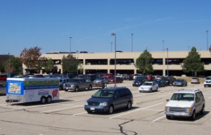 A parking lot with several cars, light posts, and trees; in front of a parking garage